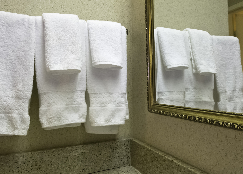 Housekeeping at a glance Five white terrycloth towels reflected by wall mirror in hotel bathroom